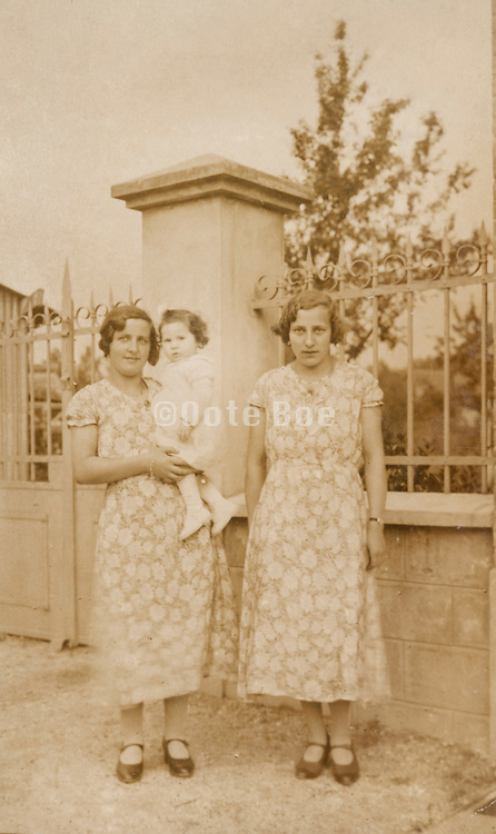 two same dressed women of which one holding a young child