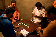 Four men playing dominoes  in Cota 200 favela, Cubatão