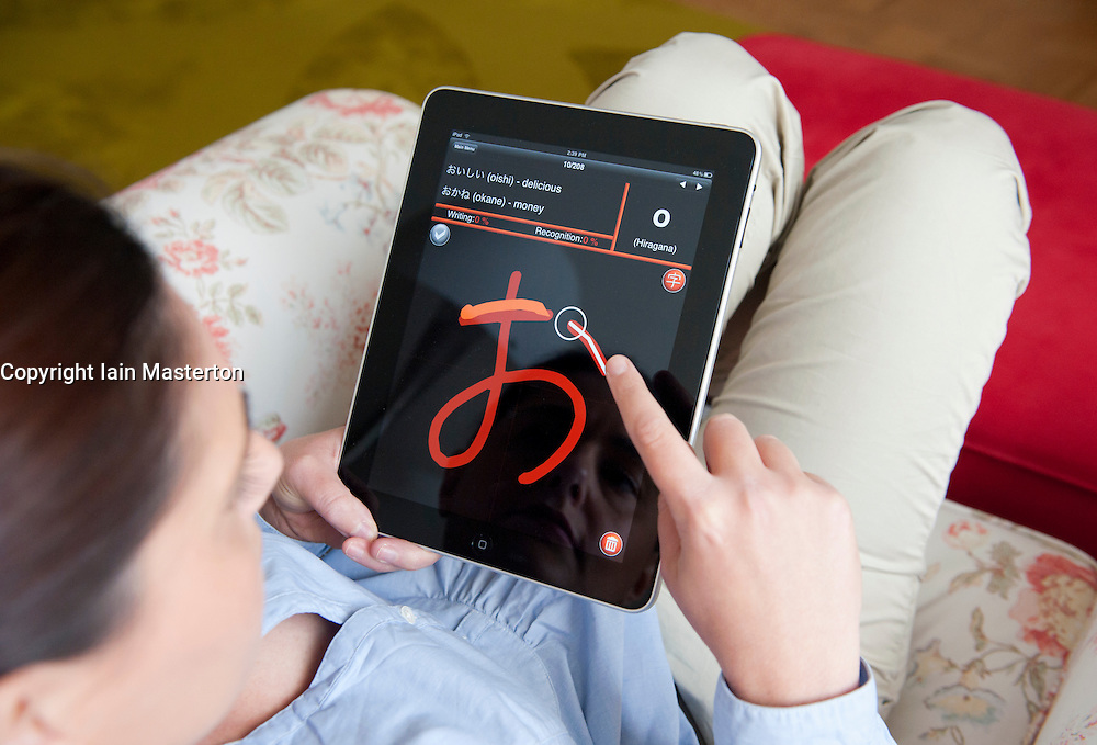 Woman using iPad tablet computer to learn Japanese language using self study language application