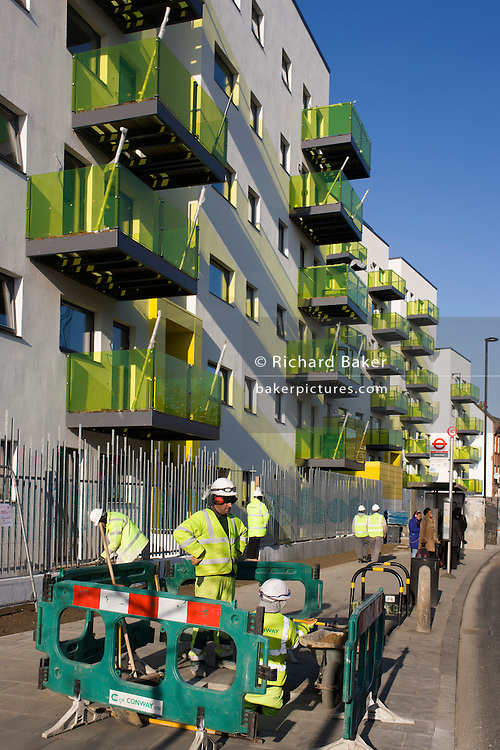 Workmen and new apartments in a block developed by Skanska in Coldharbour Lane in Camberwell, Lambeth, South London