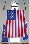 East Meadow, New York, USA. May 25, 2019. The American Flag and military flags of the United States Armed Forces - Army, Navy, Marine Corps, Air Force, Coast Guard - are suspended in the high ceiling of the Nassau County Veterans Memorial Museum, open for visitors during Saturday of Memorial Day Weekend at Eisenhower Park on Long Island.