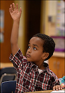 A young man raises his hands to ask a question on the first day of school. ©2013 Johny Crawford