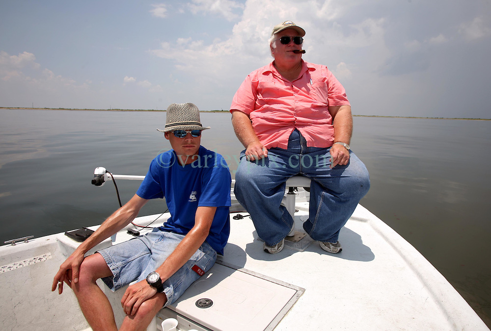 28 May 2010. Barataria Bay to Grand Isle, Jefferson/Lafourche Parish, Louisiana. <br /> Louisiana born and raised Justin Workmon (blue shirt) and Frank 'Peanut' Lensmeyer scan the eerily empty ocean where water that would ordinarily be crystal clear is now gravy coloured thanks to dispersed oil just off Grand Terre Island where Barataria Bay meets the Gulf of Mexico. Ordinarily the ocean would be filled with shrimp boats, sport fishermen, and sea birds, especially in the run up to memorial day weekend. The ecological and economic impact are devastating to the region. Oil from the Deepwater Horizon catastrophe is evading booms laid out to stop it thanks in part to the dispersants which means the oil travels at every depth of the Gulf and washes ashore wherever the current carries it. The Louisiana wetlands produce over 30% of America's seafood and are the most fertile of their kind in the world.<br /> Photo credit; Charlie Varley<br /> www.varleypix.com