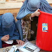 Women in burqas assemble water filters with the Female Engagement Team (FET) with a translator in a water filtration demonstration in the village of Nari, Kunar Province of Eastern Afghanistan with Waves For Water and the US Military.