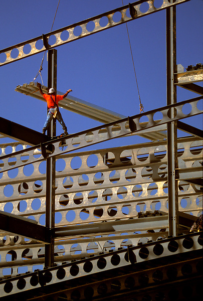 Stock photo of a worker balancing while guiding steel beams during construction of a building frame.