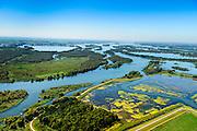Nederland, Noord-Brabant, Werkendam, 23-08-2016; Ruimte voor de Rivier project Ontpoldering Noordwaard. Foto richting Biesbosch. De bandijk (winterdijk) is voorzien van doorlaten annex brug, boerderijen zijn op terpen gebouwd. De dijken aan de rivierzijde zijn gedeeltelijk afgegraven waardoor rivier de Nieuwe Merwede bij hoogwater via de Noordwaard en de Biesbosch sneller naar zee stromen. Gevolg van de ingrepen is dat de waterstand verder stroomopwaarts zal dalen. Ook de getijden keren terug in het gebied.<br /> National Project Ruimte voor de Rivier (Room for the River) By lowering and moving the dike of the Noordwaard polder the area will become subject to controlled inundation and function as a dedicated water detention district. Houses and farmhouses havbeen demolished and rebuild  on new dwelling mounds.<br /> luchtfoto (toeslag op standard tarieven);<br /> aerial photo (additional fee required);<br /> copyright foto/photo Siebe Swart