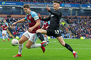 Barnsley forward Kieffer Moore (19) goes into tackle Burnley defender James Tarkowski (5) during the The FA Cup 3rd round match between Burnley and Barnsley at Turf Moor, Burnley, England on 5 January 2019.