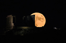 Pictured: The full moon rises next to the Poseidon Temple at the Cape of Sounion, some 70 km south of Athens, Greece on August 3, 2020. <br /> <br /> Dimitris Lampropoulos