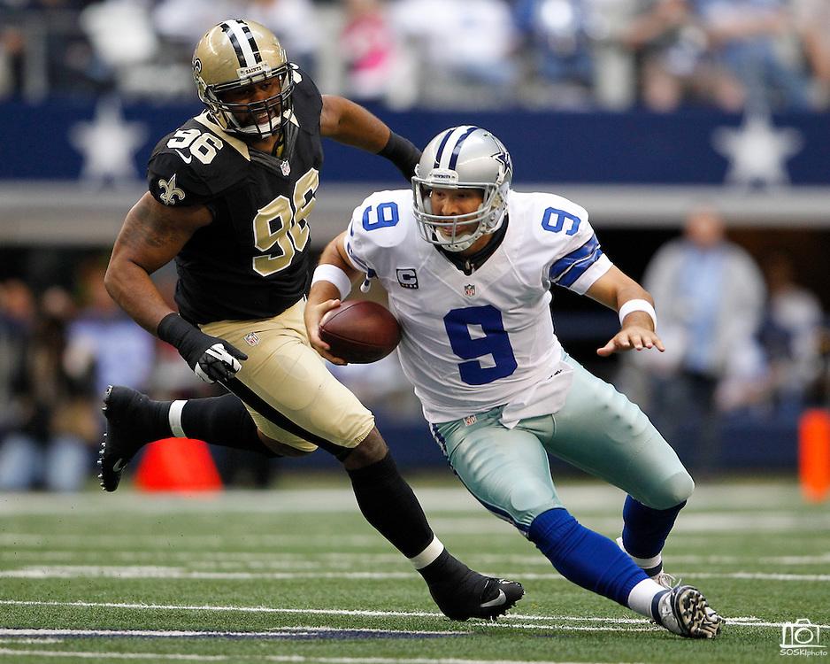 Dallas Cowboys quarterback Tony Romo (9) slips as he escapes New Orleans Saints defensive tackle Tom Johnson's (96) tackle at Cowboys Stadium in Arlington, Texas, on December 23, 2012.  (Stan Olszewski/The Dallas Morning News)