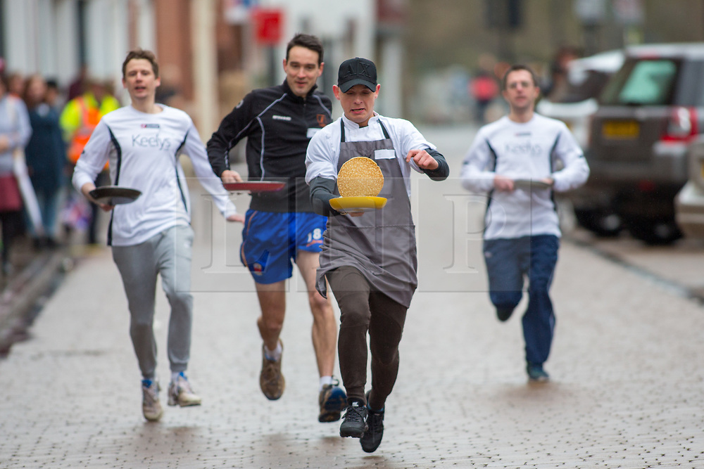 © Licensed to London News Pictures. 13/02/2018. The three hundredth (300) run of the annual Shrove Tuesday Pancake race took place in the centre of Lichfield. The race has run uninterrupted even through both world wars. Pictured, men's winner Damiean (correct) Bolkowski, a local chef, wins the main race. Photo credit: Dave Warren/LNP