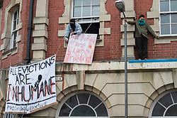© Licensed to London News Pictures; 10/03/2021; Bristol, UK. Squatters are seen at a window with banners and standing on the ledge of the first floor. Police and bailiffs try to evict a squatted building on Gloucester Road in North Bristol. The squatters say they are called The Pigeon Shit Collective, because of the Government's failings, and they are giving support to homeless people and those in need during the covid-19 coronavirus pandemic. Photo credit: Simon Chapman/LNP.