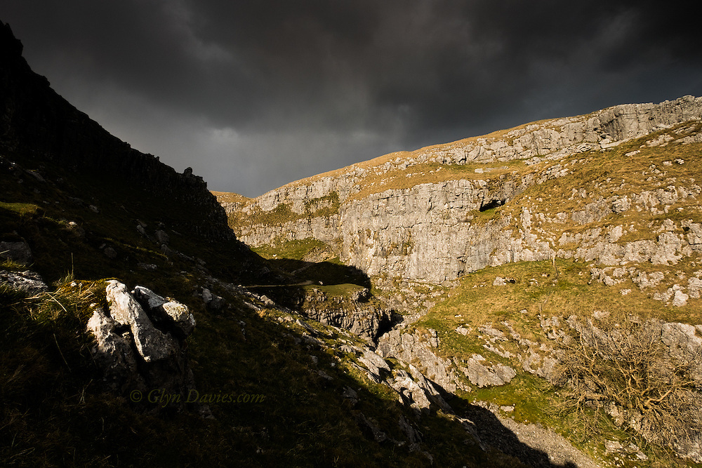 Dramatic evening sunlight catches the West facing cliffs of a limestone gorge above Malham Cove in the Yorkshire Dales. It looks warm and vibrant but the wind was arctic and sunlight was mixed with snow flurries