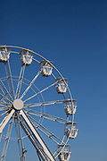 The white carriages of a fun fair big wheel ride on the 20th April 2019 in Hastings in the United Kingdom. Hastings is a town on England's southeast coast, its known for the 1066 Battle of Hastings.