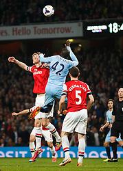 Arsenal Defender Per Mertesacker (GER) and Man City Midfielder Yaya Toure (CIV) compete in the air - Photo mandatory by-line: Rogan Thomson/JMP - 07966 386802 - 29/03/14 - SPORT - FOOTBALL - Emirates Stadium, London - Arsenal v Manchester City - Barclays Premier League.