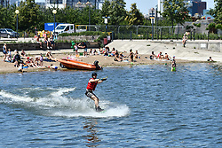 © Licensed to London News Pictures. 25/06/2020.  London UK: Londoners take to the beach at the Royal Victoria Dock in Newham, East London on the hottest day of the year so far. Bathers brave the chilling waters at the man made beach, Photo credit: Steve Poston/LNP
