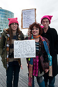 March 4th 2017. Thousands of people, mostly women and girls, marched across Tower Bridge in an event organised by Care International to mark International Womens Day March 8th and the need for gender equality. Three people wearing pink pussy hats hold a placard saying Womens Rights shouldnt be something we need to march for.