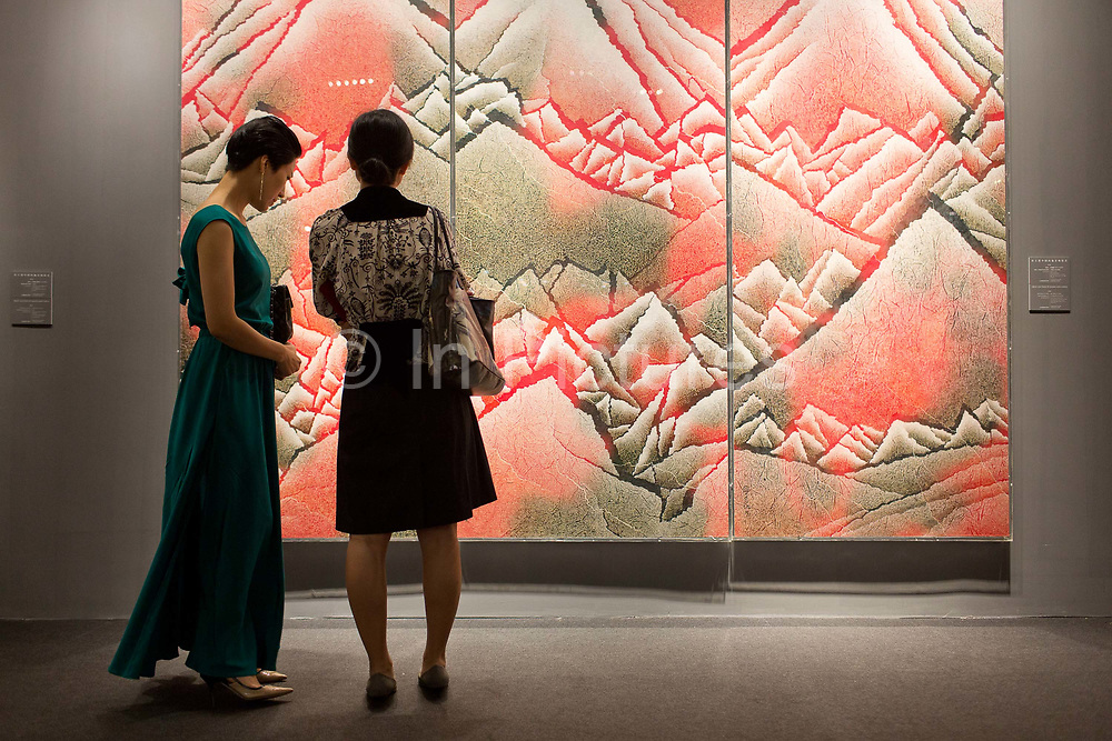 """Attendees look at artworks on display during a Christie's preview event in Shanghai, China September 04,  2013. Both Southeby's and Christie's have opened an office in Mainland China in the past year, however they face overwhelming odds as China's state-owned auction houses such as Poly and Jiamu enjoys a near monopoly over China's art procurement market as foreigners are not allowed to buy vaguely defined """"historical"""" art."""