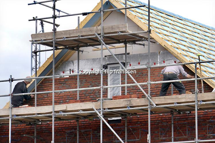 Nederland, Afferden, 15-5-2020 Nederlandse bouwvakkers zijn bezig met het metselen van de buitenmuur van huizen . De een is al wat ouder, de ander jonger . Ouderen in de bouw kunnen wat eerder met pensioen, aow, maar hun lichaam is toch al vaak versleten .Foto: Flip Franssen