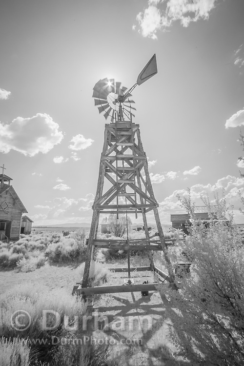 Fort Rock homestead with windmill water pump. In 1988 the Fort Rock Valley Historical Society opened the Fort Rock Homestead Village Museum which preserves and protects homestead-era structures. The buildings were moved from their original locations to the museum site just west of the town of Fort Rock., Oregon. © Michael Durham