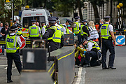 A police protestor removal unit is working to remove a member of Extinction Rebellion (XR) who glued themselves into the gates outside Houses of Parliament, Westminster Palace by Abingdon Street in London on Wednesday, Sept 9, 2020 - have been arrested ahead of Prime Minister's Questions (PMQs). Extinction Rebellion has organised a week of action to highlight the climate crisis. They say they are holding the government to account for failing to tackle the issue since declaring 2019 a climate emergency. Boris Johnson dismissed the protests at PMQs, branding the group 'a bunch of crusty left-wing anarchists'.<br /> Environmental nonviolent activists group Extinction Rebellion enters its 9th day of continuous ten days protests to disrupt political institutions throughout peaceful actions swarming central London into a standoff, demanding that central government obeys and delivers Climate Emergency bill. (VXP Photo/ Vudi Xhymshiti)