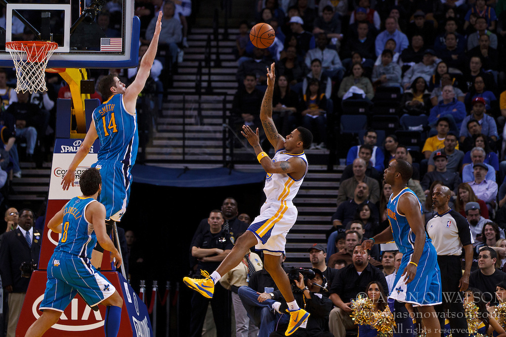 Mar 28, 2012; Oakland, CA, USA; Golden State Warriors shooting guard Brandon Rush (4) shoots over New Orleans Hornets power forward Jason Smith (14) during the second quarter at Oracle Arena. New Orleans defeated Golden State 102-87. Mandatory Credit: Jason O. Watson-US PRESSWIRE
