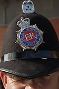 Policeman helmet, with a symbol with the words EIIR, in tribute to Elizabeth II Regina, the Queen Elizabeth. Manchester, UK.