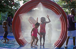 Stock photo of young children playing in tubes of spraying water