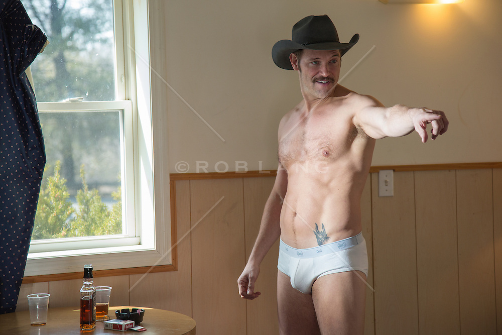 cowboy in his underwear making hand gestures while in a sleazy motel room