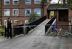 © Licensed to London News Pictures. 06/07/2021. London, UK. Police continue to guard a crime scene at a housing estate off Oval Place in south London where a 16 year old boy was stabbed to death last night. Police were called at around 23:45hrs on Monday, 5 July, to a teenager stabbed in Oval Place, SW8. Officers attended along with London Ambulance Service. The 16-year-old male was pronounced dead at the scene. Photo credit: Peter Macdiarmid/LNP