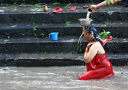 August 26, 2017 - Kathmandu, Nepal - A Hindu woman takes bath ritual to clean herself during Rishi Panchami festival on the bank of Bagmati river in Kathmandu,Nepal. Rishi Panchami, also known as Bhadraprada Sukla Panchami, is the last day of Teej Festival.On the occasion, women take a bath early in the morning to mark Rishi Panchami and seek forgiveness for 'sins' committed during monthly periods.Hindu women offer prayers to Saptarshis  (Credit Image: © Archana Shrestha/Pacific Press via ZUMA Wire)