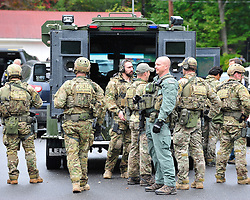 Members of the US Marshal's Special Operations Team assemble for a meeting in the parking lot of Callie's Candy Kitchen Sept. 25th, 2014 in Canadensis, Pennsylvania (Chris Post | lehighvalleylive.com)