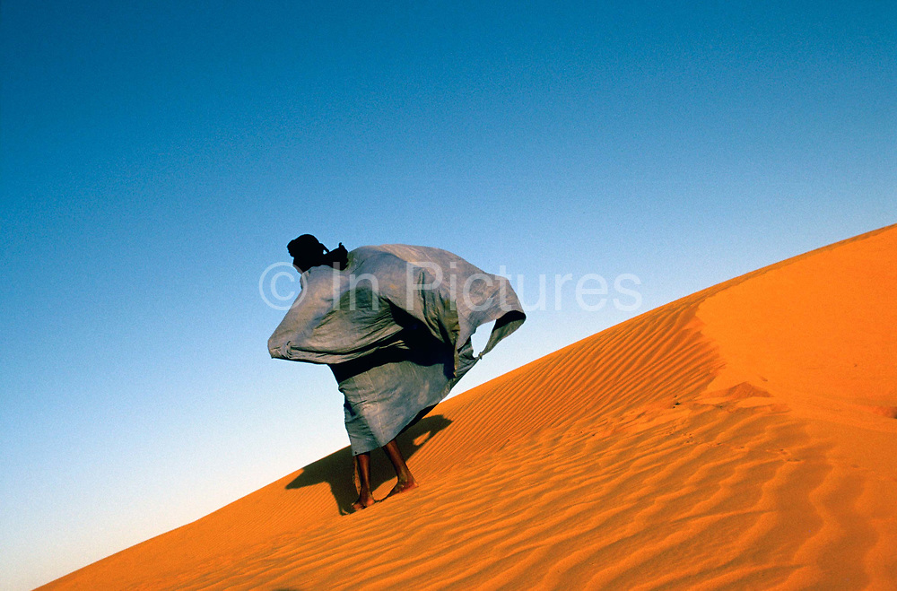 """A man walks over a dune overlooking Chinguetti,Mauritania. His Boubou flapping in the wind.<br /> Once one of Islam's holiest cities (today it is regarded as the seventh holiest city) Chinguetti has been dated at a around seven hundred, (700) years old and is famed for it's Koranic libraries and distinctive mosque, Mauritania. From the story """"The Wind and the City""""."""