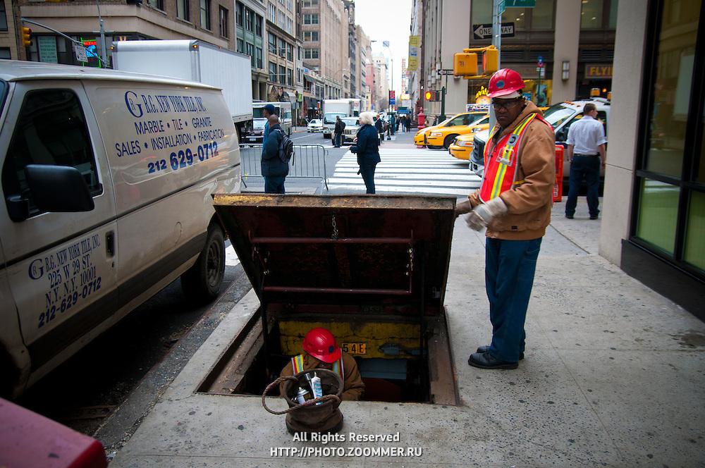 Workers get underground in Manhattan street, New York City
