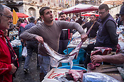 A man holds a swordfish at the Mercato della Pescheria Market in Catania, Sicily, Italy. A fish market has been held every day in Piazza Alonzo di Benedetto since the beginning of the 19th century, although there has likely been a market here for centuries. and is the most important market in Catania.