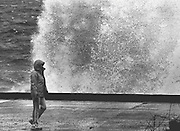 Bundled against the windy weather, a stroller along Beach Drive Southwest near Alki ignores the waves breaking against the retaining wall. (Cole Porter / The Seattle Times, 1984)