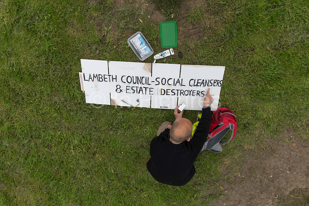 A man making a protest banner on Central Hill Estate on 17th May 2016 in South London, United Kingdom. Central Hill is a low-rise estate of more than 450 homes in Crystal Palace in South London and has been recommended for demolition under Lambeth Council estate regeneration plan. The housing scheme, builtbetween 1966 and1974, was designed by Rosemary Stjernstedt under Lambeth Council's director of architecture,Ted Hollamby.