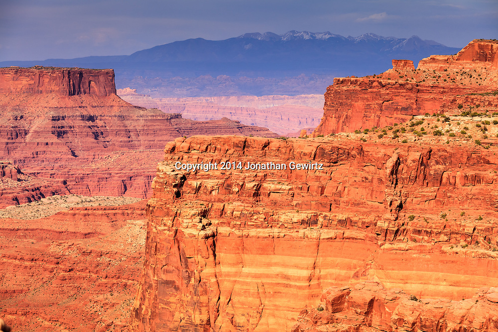 A view of red-rock canyons overlooking the Colorado River with the LaSal Mountains in the distant background, as seen from near the visitor center at Canyonlands National Park, Utah. WATERMARKS WILL NOT APPEAR ON PRINTS OR LICENSED IMAGES.<br /> <br /> Licensing: https://tandemstock.com/assets/52076616
