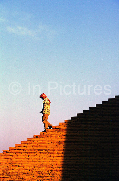 A man walks down the ziggurat at Ur, supoosedly the city of the prophet Abraham's birth. Ur was a principal city of ancient Mesopotamia.<br /> The Ziggurat was dedicated to the moon and was built approximately in the 21st century BC by king Ur-Namma. In Sumerian times it was called Etemennigur.