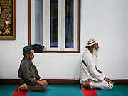10 JULY 2015 - BANGKOK, THAILAND:  Men pray after Iftar at Haroon Mosque in Bangkok. Iftar is the evening meal when Muslims end their daily Ramadan fast at sunset. Iftar is a communal event at Haroon Mosque and hundreds of people usually attend the meal.    PHOTO BY JACK KURTZ