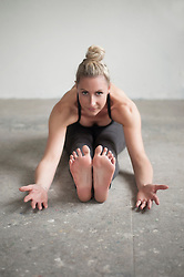 Mid adult woman practicing seated forward bend pose in yoga studio, Munich, Bavaria, Germany