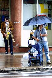 Artista de rua toca sax protegido da chuva debaixo de uma marquise na rua Ramiro Barcelos na zona norte da cidade de Porto Alegre. FOTO:  Jefferson Bernardes/Preview.com