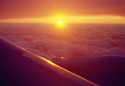 View of airplane wing out of window at sunset over clouds