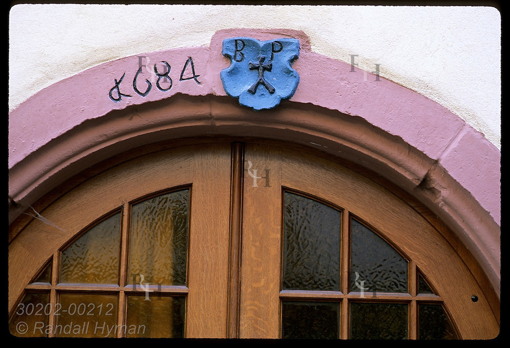 Ancient script over arched door dates from Roman address system in the town of Eguisheim, Alsace France