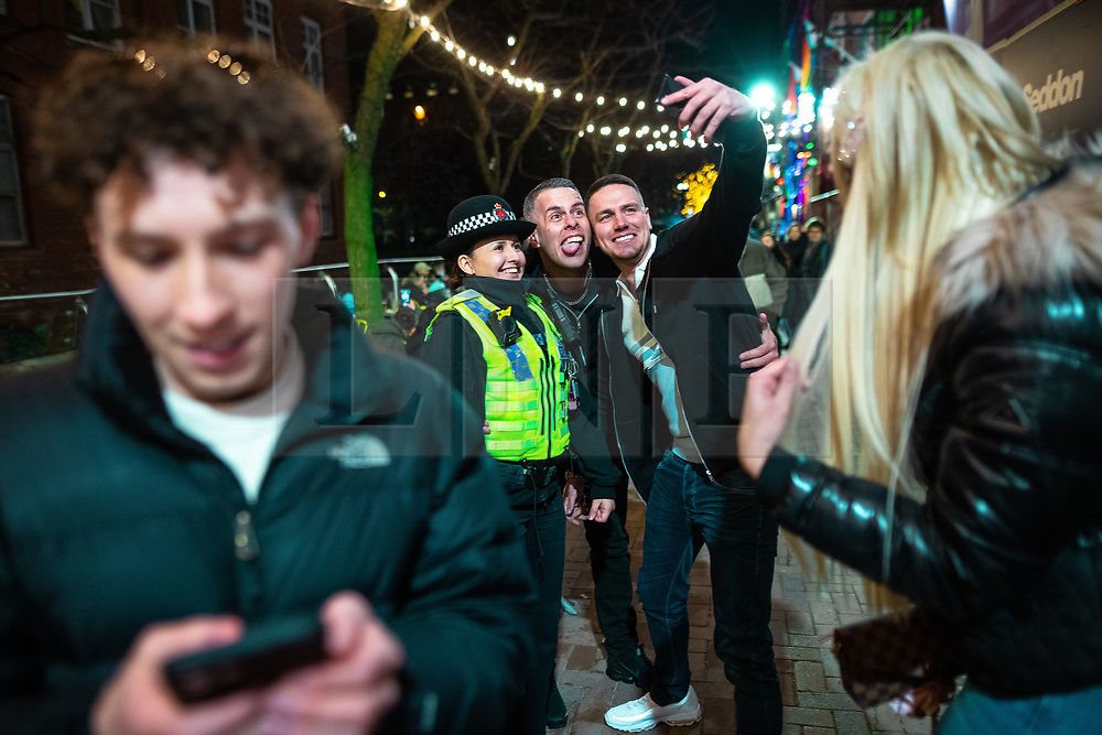 © Licensed to London News Pictures. 12/04/2021. Manchester, UK. Friends pose for a selfie with a police officer on patrol on Canal Street . People on a night out in Manchester City Centre as government restrictions to control the spread of Coronavirus are eased across the UK. Pubs, restaurants, hairdressers, gyms and non essential retailers are now permitted to serve customers within restrictions. Photo credit: Joel Goodman/LNP