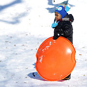 A young boy sledding in Central Park after New York City was hit with over 7 inches of snow during its first winter storm of the year. Central Park, Manhattan, New York, USA. 4th January 2014 Photo Tim Clayton