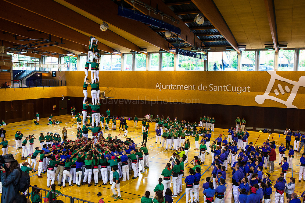 Castellers in Sant Cugat, Barcelona, Catalonia, Castellers making a castell in Sant Cugat - the Catalan tradition of building human towers. The strongest keep the bottom steady, while a small child, climbs to the top to complete the castell by adopting a pose.One Castell can be made up of hundreds of people.  In 2010,  UNESCO to be amongst the Masterpieces of the Oral and Intangible Heritage of Humanity.