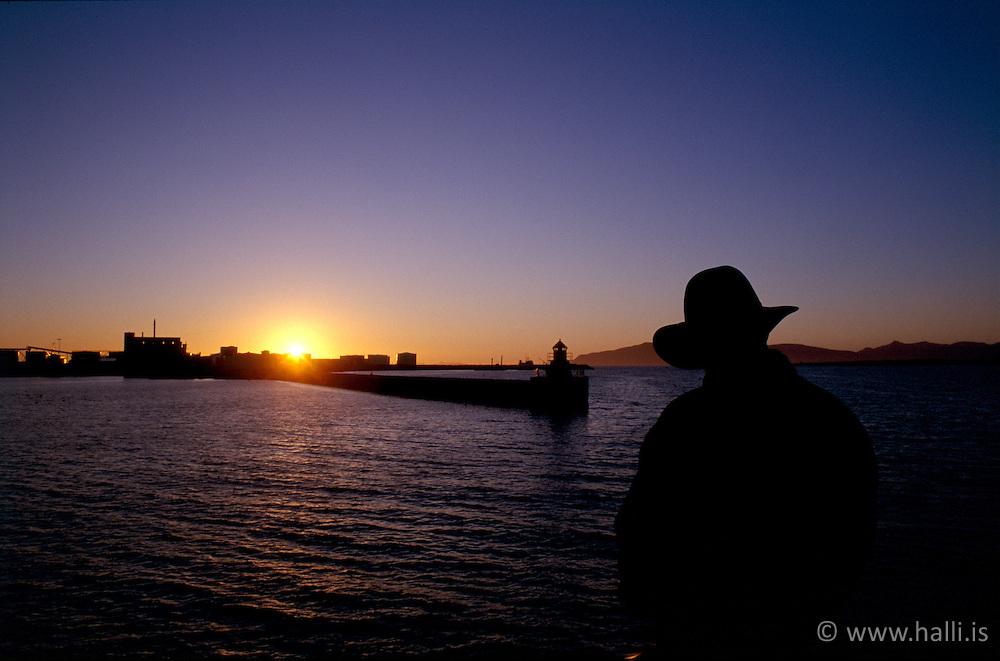 Maður horfir á sólsetur frá höfninni í Reykjavík / Man watching the sunset from Reykjavik harbour