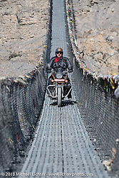 Danny Ochs riding across a narrow suspension bridge over the Kali Gandaki River on day-6 of our Himalayan Heroes adventure riding from Muktinath to Tatopani, Nepal. Sunday, November 11, 2018. Photography ©2018 Michael Lichter.