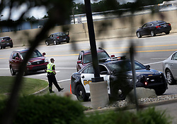 June 21, 2017 - Flint, Michigan, U.S. - A Flint Township police officer redirects traffic at the closed Bishop International Airport in Flint after a police officer was stabbed earlier in the day on Wednesday. The stabbing is being investigated by the FBI as a possible terror attack, officials said. The suspect is in custody and is being questioned. (Credit Image: © Detroit Free Press via ZUMA Wire)