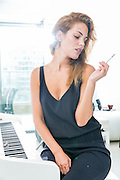 Young woman smokes a cigarette indoors